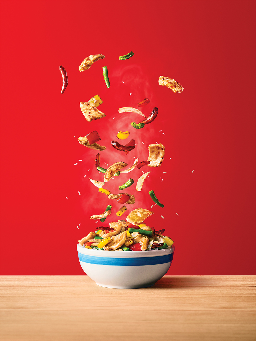 Panda Express Firecracker Chicken Bowl with flying ingredients on a wooden table.